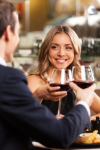 Beautiful couple having romantic dinner at restaurant. smiling woman looking at man dinking wine at toast